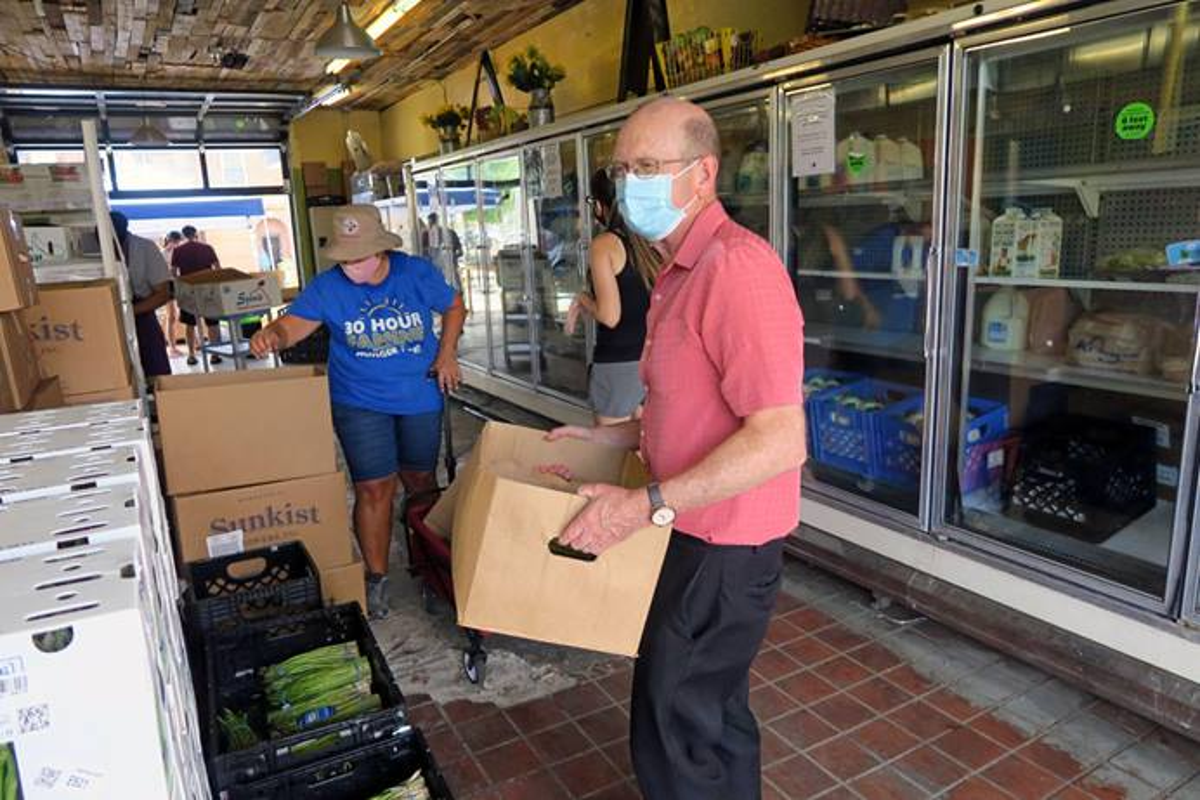 El Rev. John Edgar, director ejecutivo de Desarrollo Comunitario para Todas las Personas en Columbus, Ohio, agrega un galón de leche a una caja de alimentos empacada para uno/a de los/as cientos de clientes que obtienen alimentos diariamente de la organización. Foto cortesía de Desarrollo Comunitario para Todas las Personas.