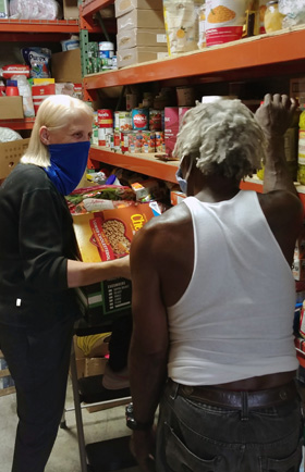 The Rev. Faith Fowler, executive director of Cass Community Social Services and senior pastor of Cass Community United Methodist Church in Detroit, speaks with volunteer Ke Ke Sacada while preparing to load a van for free grocery deliveries. Photo by Samantha Funk.