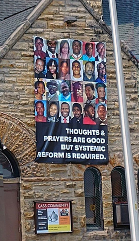 A banner promoting systemic reform to address racial issues hangs on the wall of Cass Community United Methodist Church in Detroit. Photo by Cortez Perry.