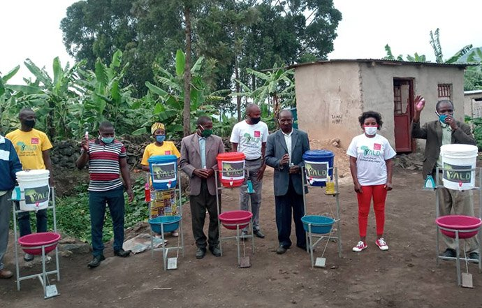 Members of Young Africa Leadership Development and Emmaus United Methodist Church stand by handwashing stations in Gisenyi, Rwanda. The supplies were provided as part of the young leader group's COVID-19 awareness campaign. Photo courtesy of Peter Cibuabua, Young Africa Leadership Development.