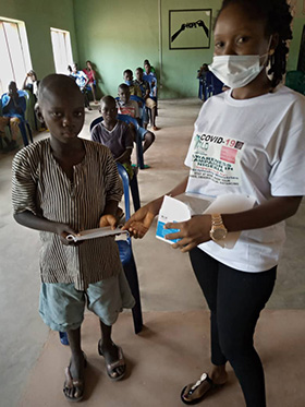 Jenifer Philip, a Young Africa Leadership Development member, distributes face masks to children at the church's orphanage in Jalingo, Nigeria. Photo courtesy of Peter Cibuabua, Young Africa Leadership Development.