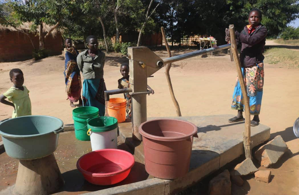 Veronika Mwale (right) pumps water from a borehole in Thako village in Mchinji, Malawai. The borehole, which supplies water for three villages, was built through a partnership between Ankeny United Methodist Church in Ankeny, Iowa, and the Malawi Provisional Conference. Photo by Francis Nkhoma, UM News.