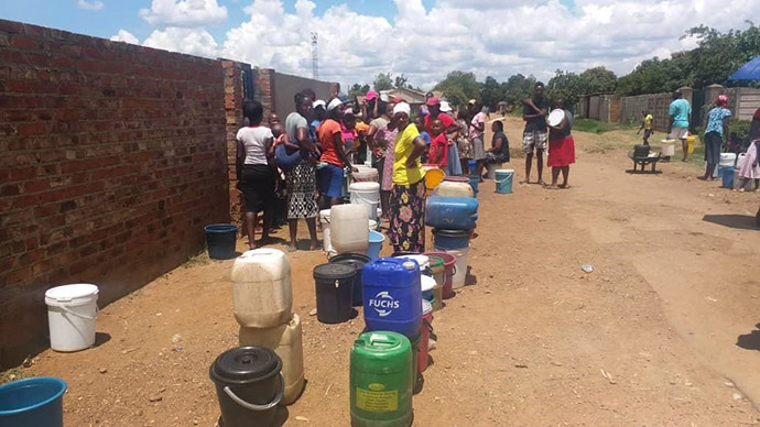 Community members wait in line to fetch water from the bolehole at Highglen United Methodist Church in the suburbs of Harare, Zimbabwe. Photo by Chenayi Kumterera, UM News.