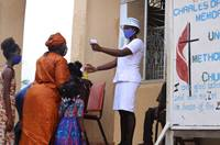 A churchgoer's temperature is taken before she is allowed into the worship service at Charles Davies United Methodist Church in western Freetown, Sierra Leone, on July 19. Wearing masks and temperature checks are among the new guidelines for churches as the government lifted the ban on congregational worship. Photo by Phileas Jusu, UM News.