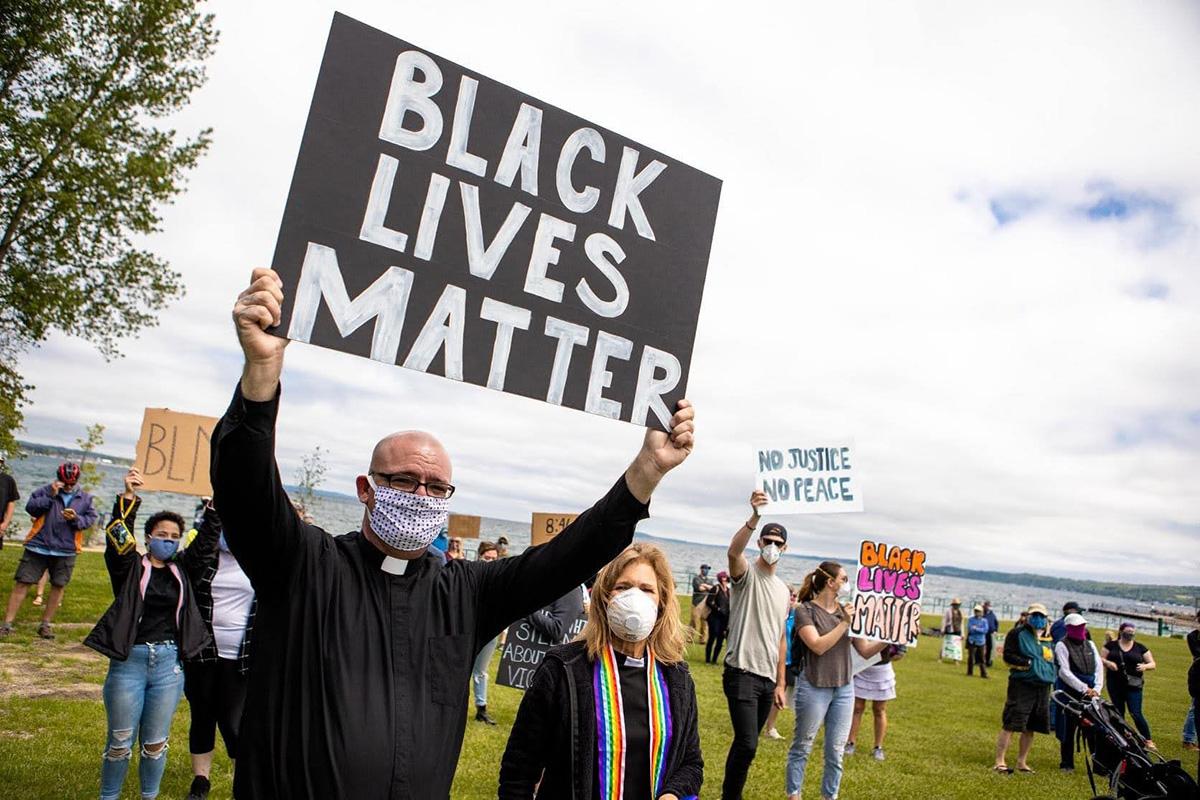 O Rev. Jeremy Wicks (frente) participa de uma demonstração do Black Lives Matter no norte do Michigan. Wicks serviu como capelão da polícia, policial da reserva e organizador da Black Lives Matter. Foto cortesia do Rev. Jeremy Wicks.