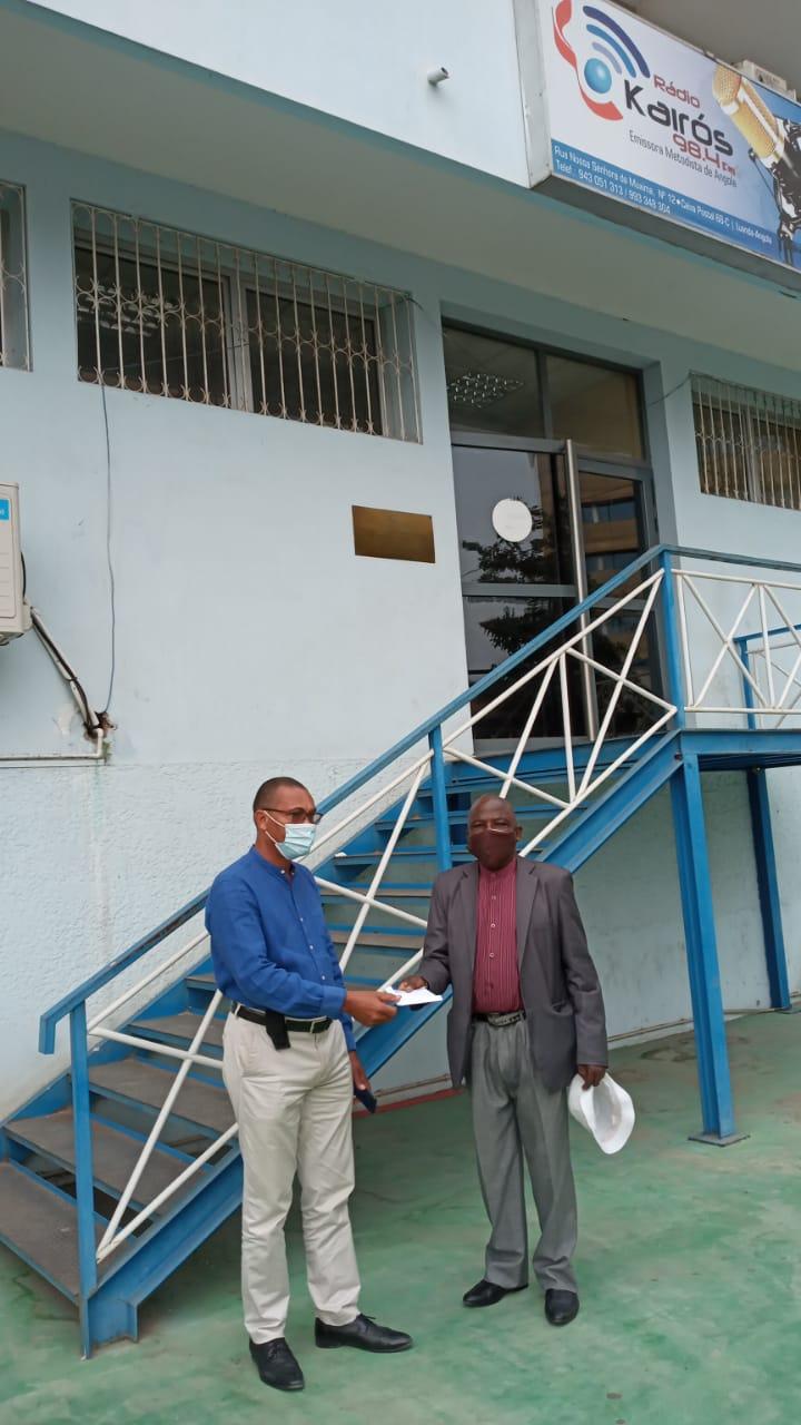 Doador fazendo entrega da sua doação ao Presidente do Conselho de Finanças do Oeste Nabeiro Mateus, em frente à Rádio Kairós-Luanda. Foto Augusto Bento.