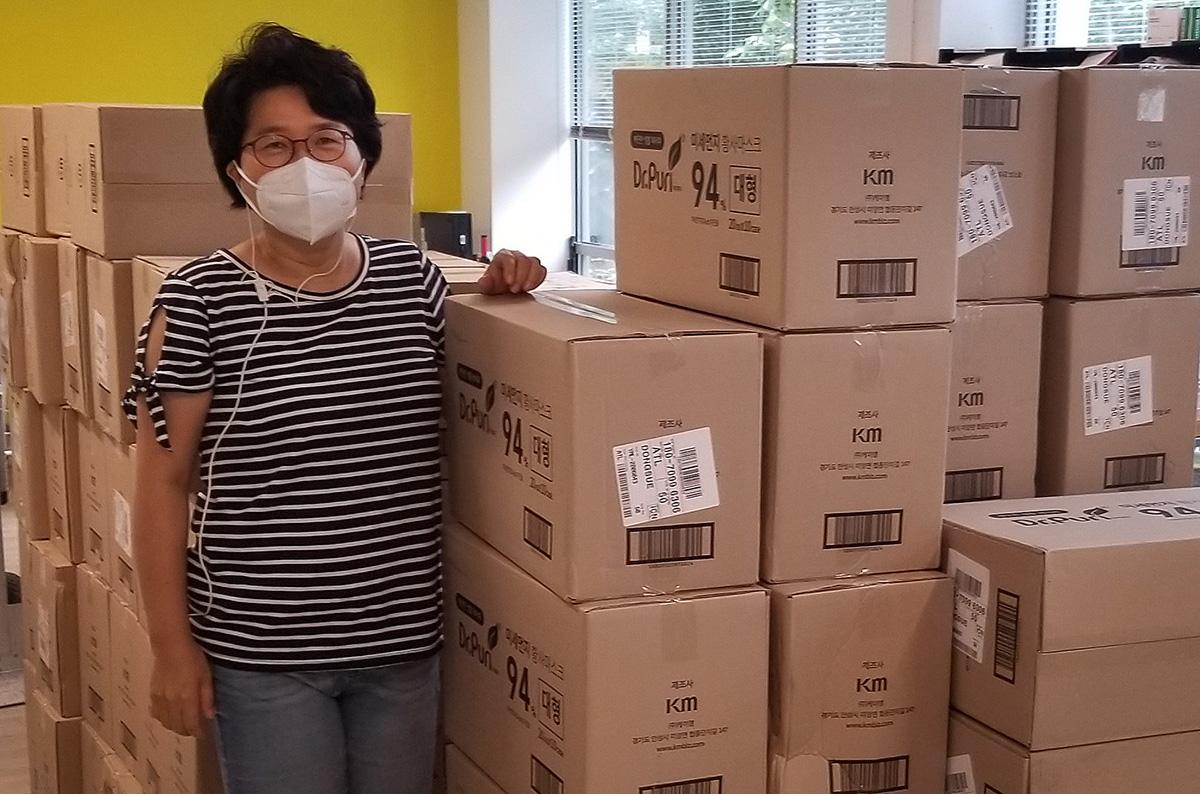 Grace Choi, actual misionera de Ministerios Globales en residencia y ex alumna de Yonsei, posa al lado de muchas cajas que contienen las máscaras donadas. Choi trabajó en el Hospital Severance Yonsei antes de convertirse en misionera. Foto cortesía de Grace Choi, GBGM.