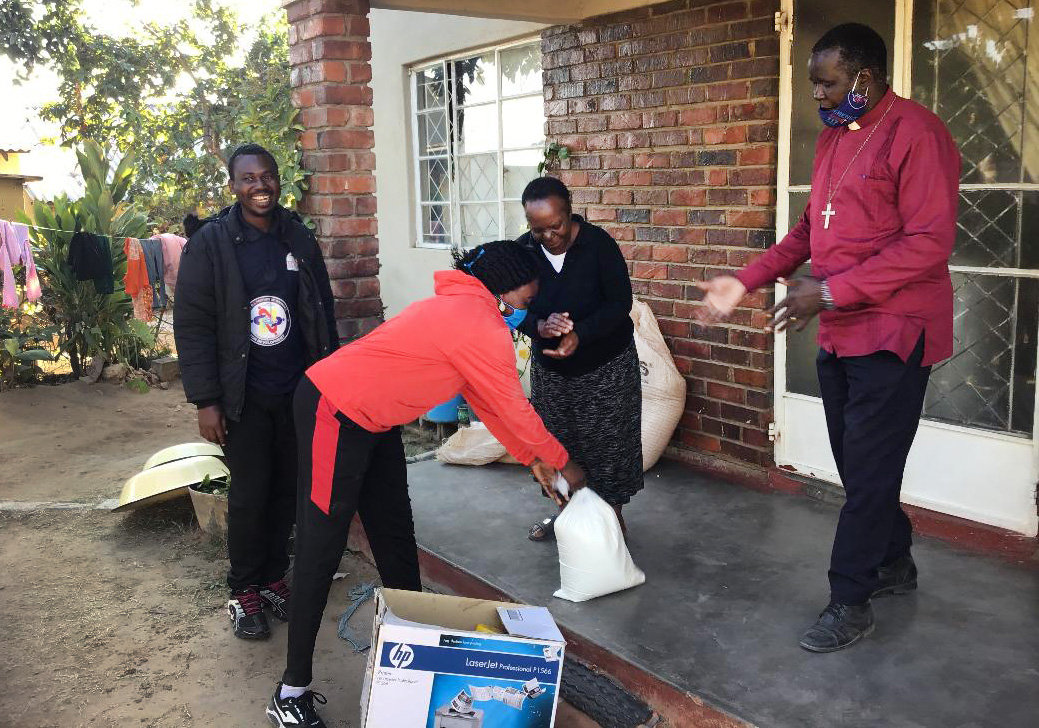 Everlyne Kukah Esther, an Africa University student from Kenya, hands over food to Charity Chikukwa, a beneficiary of the Feed a Family program in Gimboki, Zimbabwe. The Rev. Joseph Charinge (red shirt) and AU student Fiston Okito from Congo look on. Esther and her classmates started the campaign to help vulnerable families struggling during the coronavirus pandemic. Photo by Chenayi Kumuterera, UM News.
