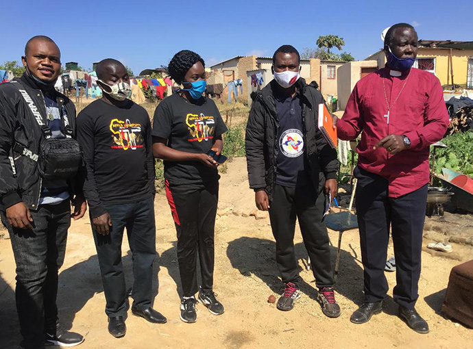 Africa University students Cesar Lodiha Akoka from Congo (from left), Barde Danjuma from Nigeria, Everlyne Kukah Esther from Kenya, Fiston Okito from Congo and the Rev. Joseph Charinge gather before distributing food to families in Gimboki, Zimbabwe, a preaching point community of St. James Dangamvura United Methdoist Church. Charinge, pastor of Gimboki UMC, said the Feed a Family campaign started by the students has resulted in six people joining his church. Photo by Chenayi Kumuterera, UM News.