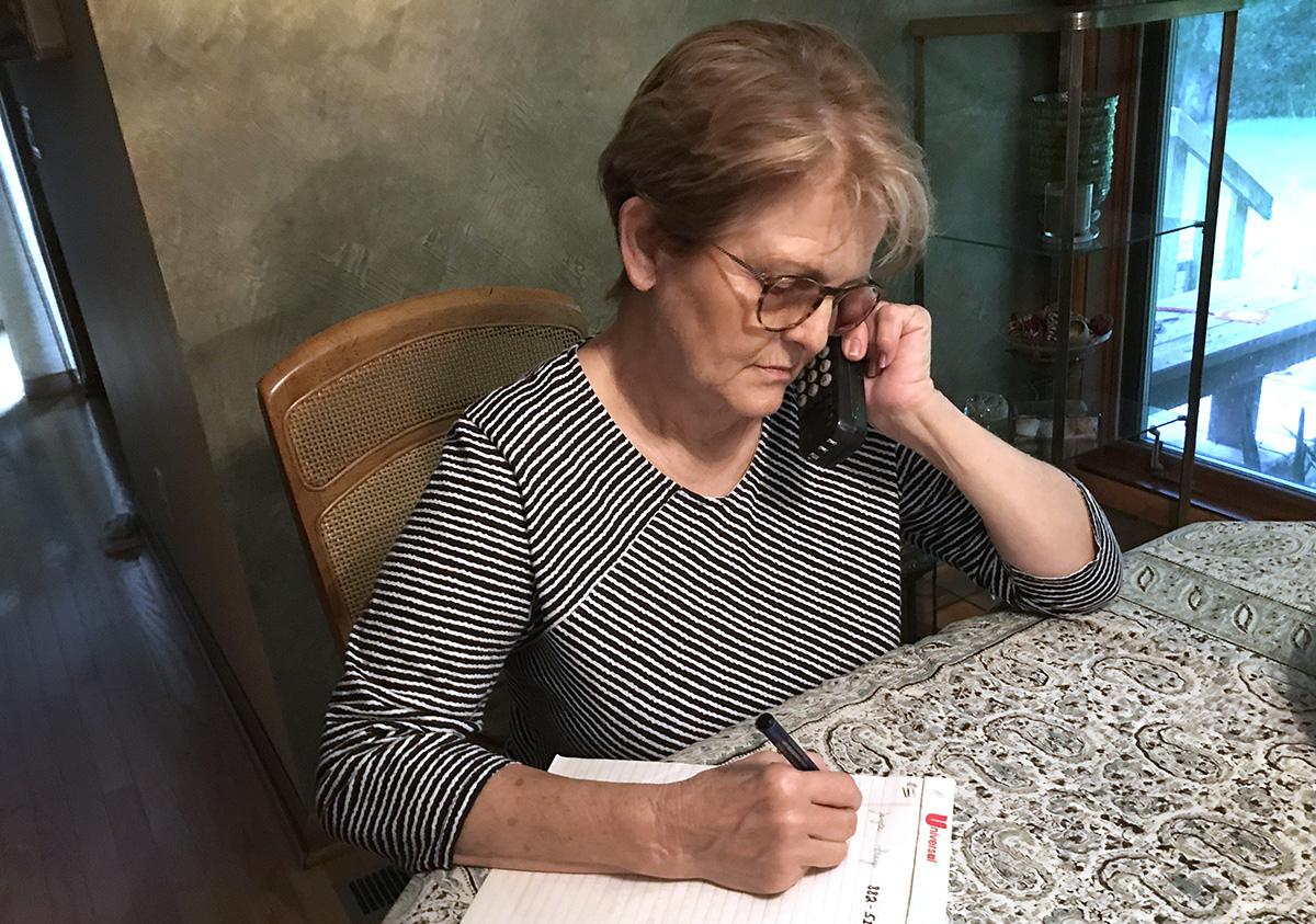 """Linda Dobbyn, paroquiana da Primeira Igreja Metodista Unida de Vincennes, em Vincennes, Indiana, usa um novo serviço chamado Sermão por Telefone para ouvir um sermão do Rev. Matt Swisher intitulado """"Liderando por Servir"""". Foto de Richard Dobbyn."""