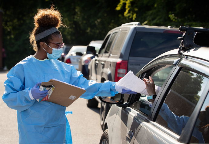 Tamera Thomas hands out paperwork to people waiting for a COVID-19 test at a drive-thru site offered by Meharry Medical College at St. Luke Christian Methodist Episcopal Church in Nashville. Thomas is a dental student at the medical school. Photo by Mike DuBose, UM News.