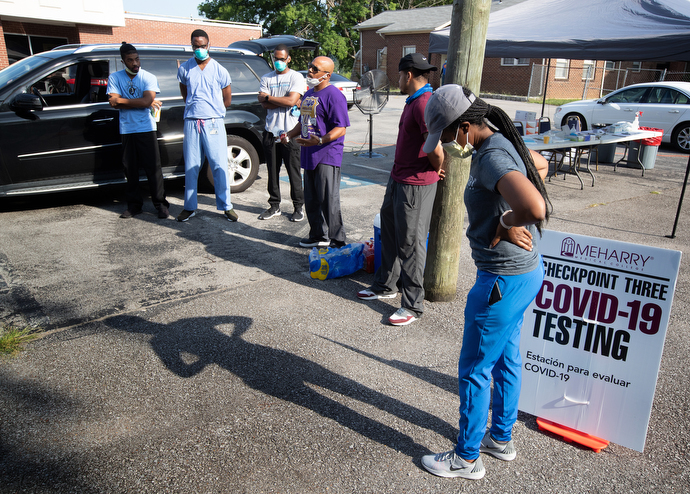Dr. Millard Collins (center, in purple t-shirt) offers a prayer and last-minute instructions before the opening of a drive-thru testing site for COVID-19 at St. Luke Christian Methodist Episcopal Church in Nashville. Collins is the chair of family medicine at Meharry Medical College. Photo by Mike DuBose, UM News.