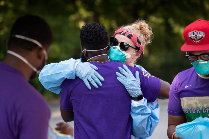 Volunteer Hannah LaBrecque (center) hugs a fellow volunteer as they don protective equipment before the opening of a drive-thru testing site for COVID-19 at St. Luke Christian Methodist Episcopal Church in Nashville. LaBrecque regularly joins a volunteer team from Meharry Medical College in Nashville to provide pop-up testing sites on Saturdays at area churches. Photo by Mike DuBose, UM News.