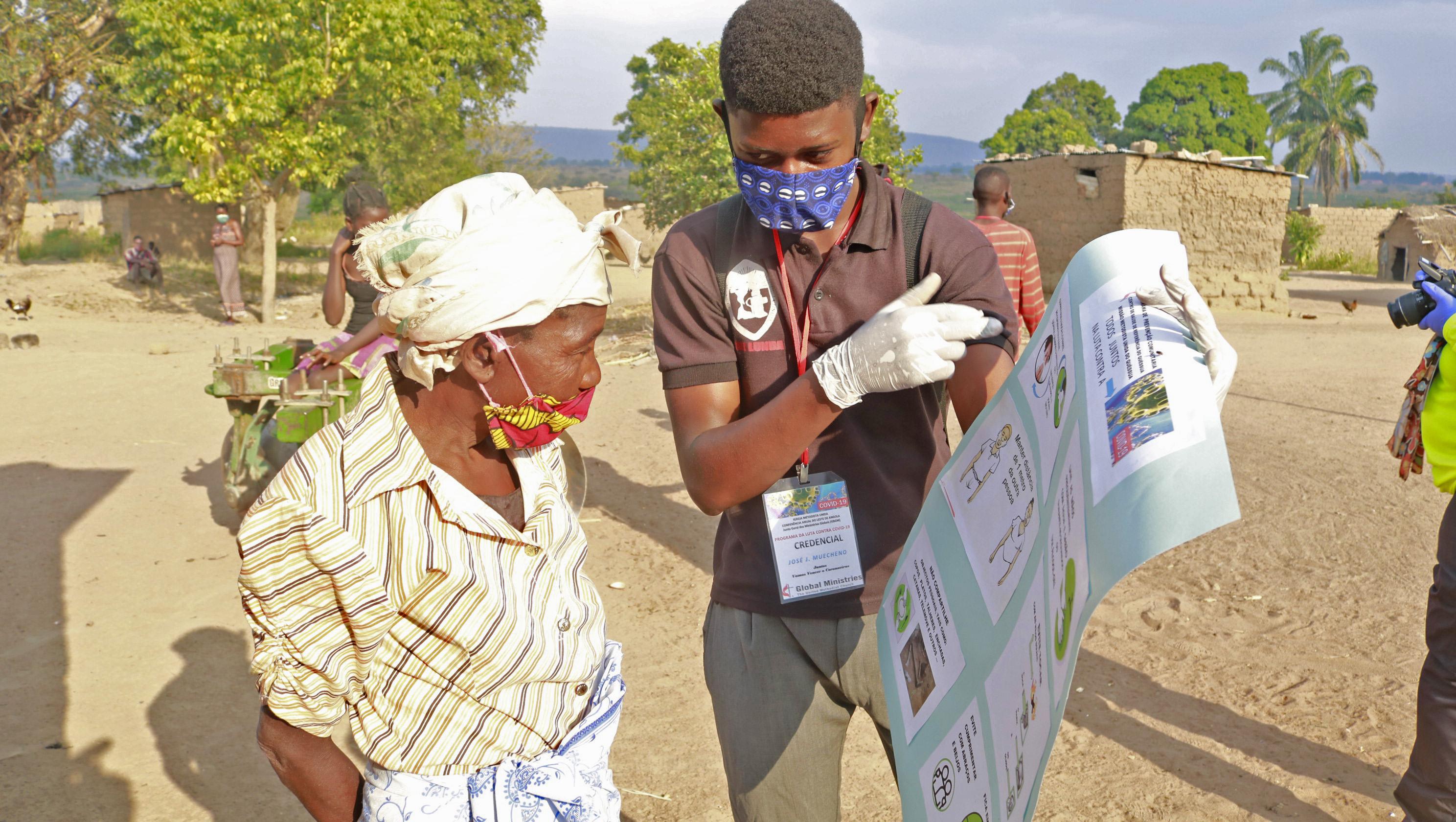Irmão José Lunda explicando à uma anciã da Aldeia do Mbango sobre COVID-19 e sobre o que deve fazer para prevenir-se dela. Foto de João Nhanga.