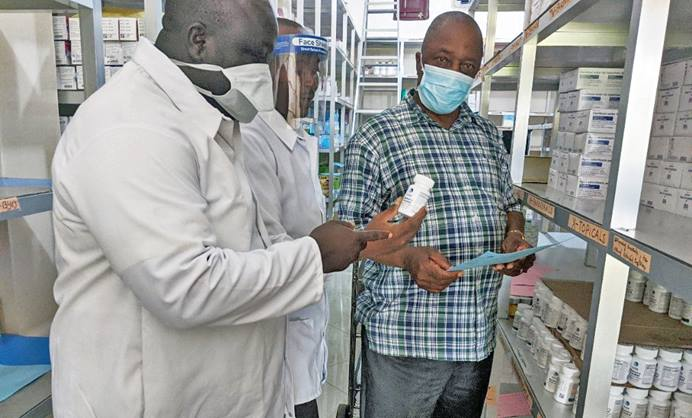 Allen S.D. Zomonway (right), a registered nurse and Ganta United Methodist Hospital administrator, reviews drug stocks with staff in the hospital pharmacy. During the pandemic, the Africa University graduate ensures that all hospital employees wear masks and take other necessary precautions. Photo courtesy of Africa University.