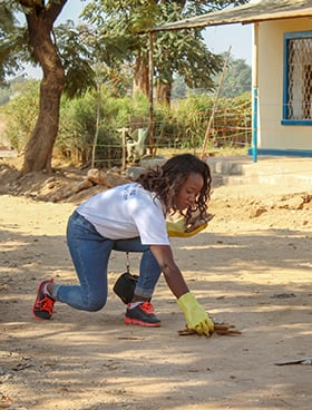 Elalie Tshipeng Kambaj, an AU alumna, picks up debris as part of a community service project in Lubumbashi, Congo. In her role as a health service administrator, she mediates between the South Congo Conference health facilities and the United Methodist Health Board. Photo courtesy of Africa University.