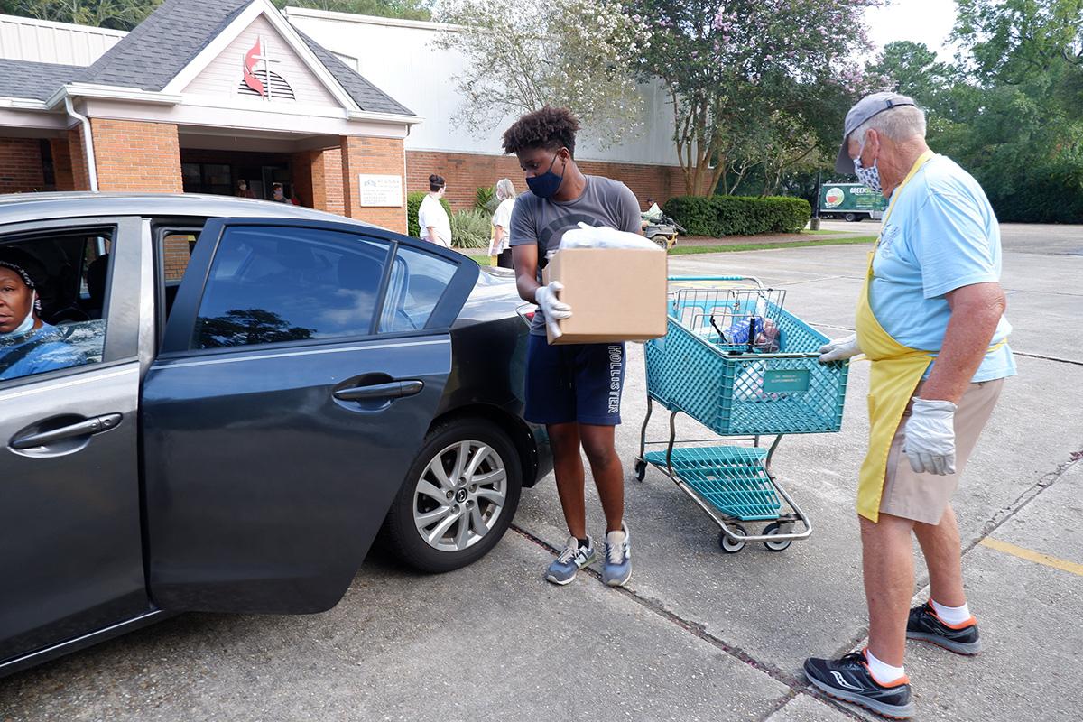 David Idikwu, à esquerda, e Phil Slicker carregam mantimentos no carro de um cliente no The Shepherd's Market, um ministério da Igreja Metodista Unida de St. John em Baton Rouge, La. Idikwu e Slicker, membros da igreja, são voluntários na despensa semanal de alimentos. Foto da Revda. Lane Cotton Winn.