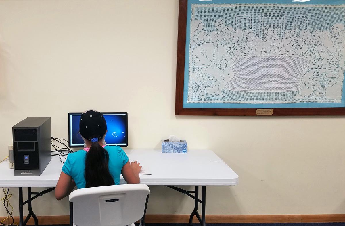 Sarai Moreno, aluna do sétimo ano, faz o dever de casa em um computador na Robbinsville Igreja Metodista Unida na Carolina do Norte. A igreja tem trabalhado para fornecer acesso ao ensino remoto em um condado rural onde mais da metade das famílias não têm internet. As mulheres na igreja criaram a última ceia bordada à direita. Foto do Rev. Eric Reece.