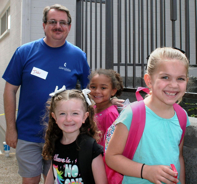 The Rev. Dan Hurlbert in this photo from before COVID-19 stands with children who have received backpacks from Prescott United Methodist Church in Arizona. This year, the church is giving away laptops to families who will return to school using only remote learning. Photo courtesy of the Rev. Hurlbert.