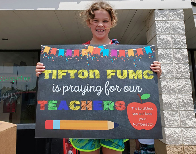 Katherine Paulk holds up a sign from Tifton First United Methodist Church in south Georgia that announces the church is praying for teachers. United Methodist congregations across the United States are finding ways to help schools address the challenges presented by COVID-19. Photo courtesy of Allison Lindsey, South Georgia Conference.