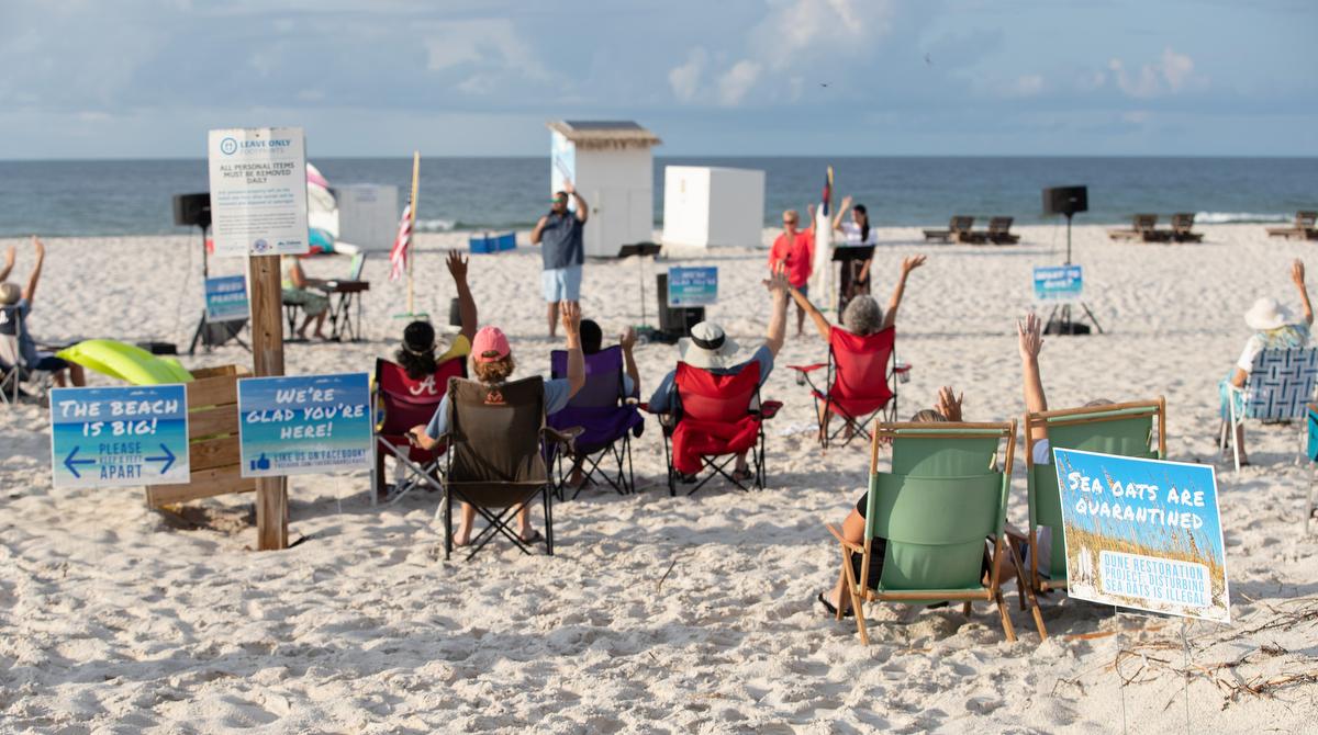 """Los/as fieles levantan los brazos en alabanza durante el servicio en playa """"Galilea"""", un ministerio de la IMU de Foley en el parque estatal Gulf, estado de Alabama. Foto Mike DuBose, Noticias MU."""