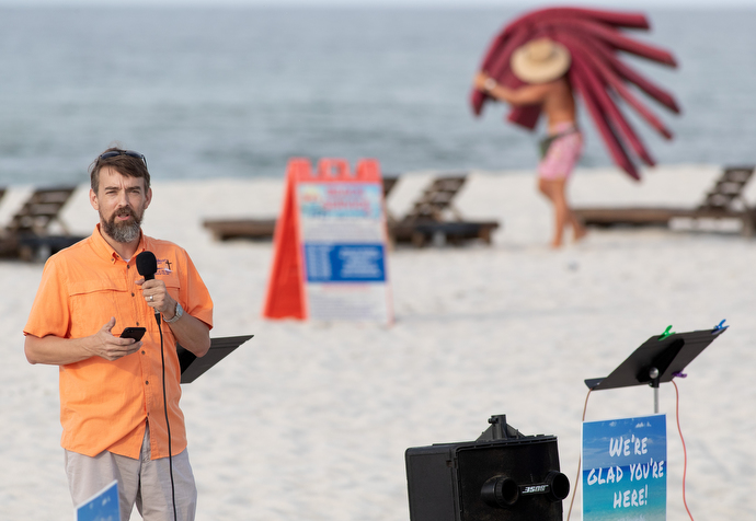 The Rev. Nolan Donald gives the sermon during the Galilean Beach Service while a beach attendant lays out chair cushions in the background. The 7:30 a.m. service is over before most other beachgoers arrive. Photo by Mike DuBose, UM News.