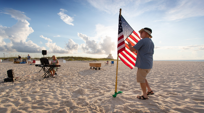Bob Cristopher unfurls the U.S. flag prior to the Galilean Beach Service while Sherrie Lynn Brewer warms up on the keyboard. Photo by Mike DuBose, UM News.