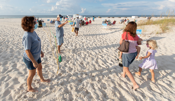 Greeters Diane and Darryl Bunch (left) welcome worshippers to the Galilean Beach Service. Photo by Mike DuBose, UM News.