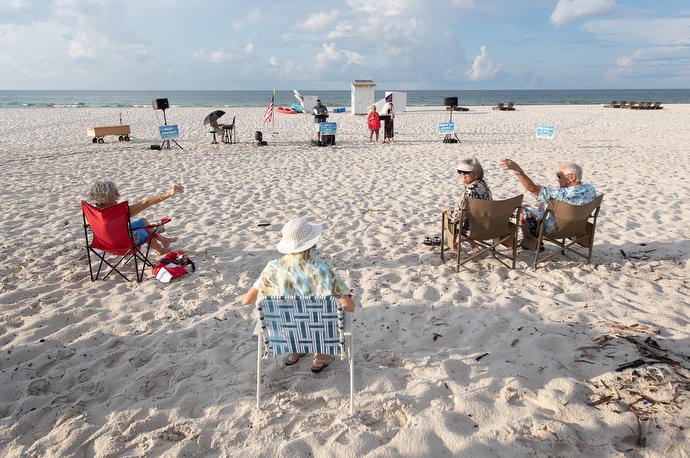 Worshippers greet one another from a distance at the Galilean Beach Service. Photo by Mike DuBose, UM News.