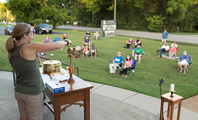 The Rev. Steph Dodge blesses the elements of Holy Communion during an outdoor worship service at Glendale United Methodist Church in Nashville, Tenn. Photo by Mike DuBose, UM News.