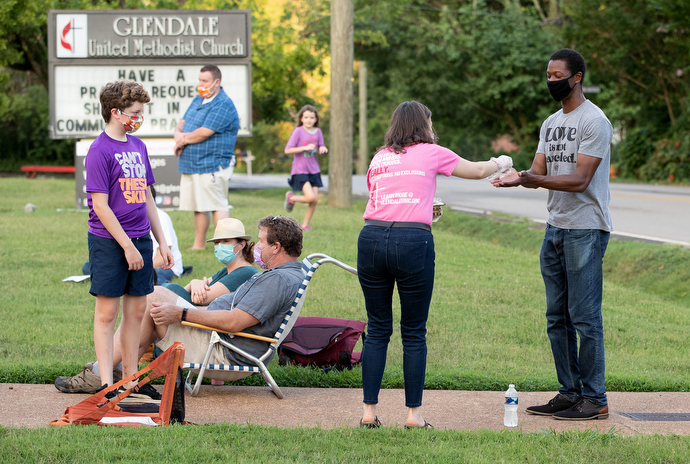 Laura Kreiselmaier serves Holy Communion to James Poland (right) during an outdoor worship service at Glendale United Methodist Church in Nashville, Tenn. Photo by Mike DuBose, UM News.