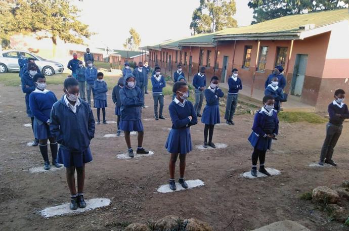 Os alunos usam máscaras e observam o distanciamento social enquanto recebem sua orientação diária antes de começar as aulas na Escola Primária Port Edward em Durban, África do Sul. Foto de Nandipha Mkwalo, Noticias MU.