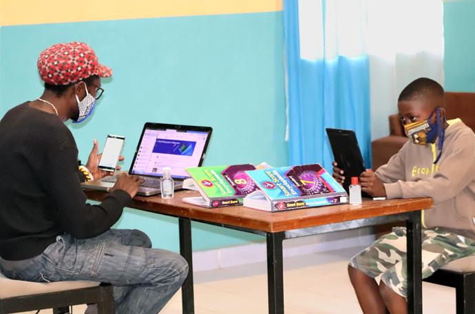 Boneface Ndira (a esquerda) trabalha com Rooney Ndung'u, 13 anos, na Igreja Metodista Unida de St. John em Nairobi, Quénia. Ndira, um membro da juventude na igreja, dirigiu o desenho de Darasani, uma aplicação de educação virtual que ajuda mais de 300 estudantes em todo o país. Os estudantes vêm em turnos para acessarem a internet na igreja enquanto assistem as suas aulas virtuais no meio da semana. Foto de Gad Maiga, Noticias MU.