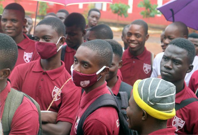 Os alunos da Academia Albert da Metodista Unida em Freetown, Serra Leoa, escutam o Director Junisa Vandy enquanto ele explica as directrizes para os Exames de Certificação da Escola Sénior da África Ocidental. Os alunos, como muitos em outros lugares em locais públicos em Serra Leoa, ainda não se adaptaram totalmente ao uso de máscaras. Foto de Phileas Jusu, Noticias MU.