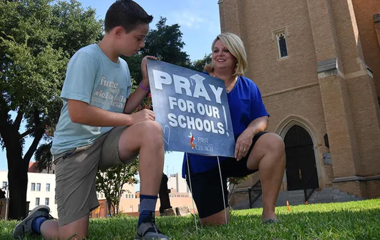 """Parker Deal y su madre Joy Deal posan al lado de uno de los carteles """"Ore por nuestras escuelas"""", distribuido por la Primera Iglesia Metodista Unida. Foto cortesía de Torin Halsey de Times Record News."""
