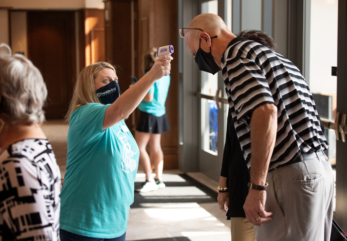 Volunteer Jennifer Jannetty checks James Crigger's temperature as he arrives for worship at Franklin First United Methodist Church. Photo by Mike DuBose, UM News.
