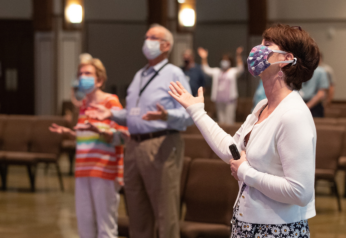 Barbara Layden (front) joins with other parishioners in giving praise during worship at Franklin First United Methodist Church. The church has adopted safety protocols, including no congregational singing, to help prevent the spread of COVID-19. Photo by Mike DuBose, UM News.