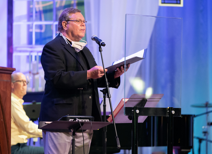 Dave Hintz sings from behind a plexiglass barrier during worship at Franklin First United Methodist Church. The church has adopted safety protocols, including no congregational singing, to help prevent the spread of COVID-19. Hintz is a member of the church's chancel choir. Photo by Mike DuBose, UM News.