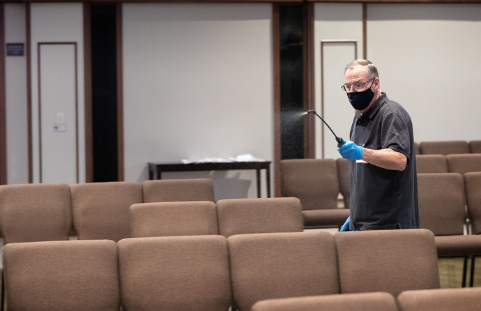 Kevin Gilmartin sprays disinfectant between services at Franklin First United Methodist Church. Photo by Mike DuBose, UM News.