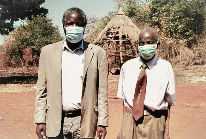 Joel Makombe, right, poses for a photo with his pastor, the Rev. John Chinyerere, in Mutare, Zimbabwe, during the COVID-19 pandemic. Makombe recalls some differences between this pandemic and the 1918 Spanish flu. Photo by the Rev. Taurai Emmanuel Maforo, UM News.