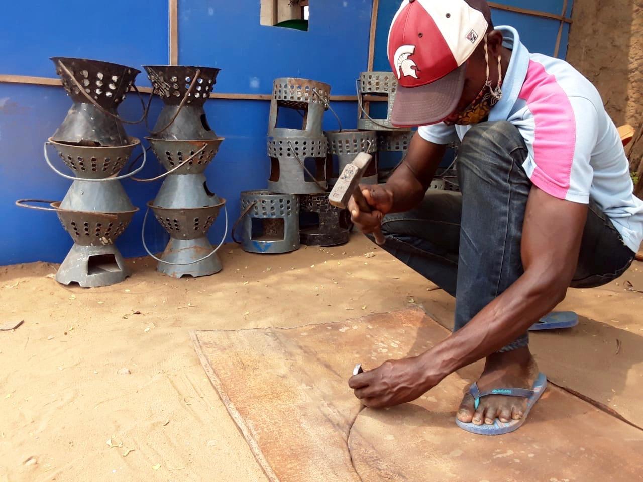 Mestre Mbala trabalha uma chapa reciclada fazendo o contorno para a produção de fogão em Luanda, Angola. Foto de Augusto Bento.