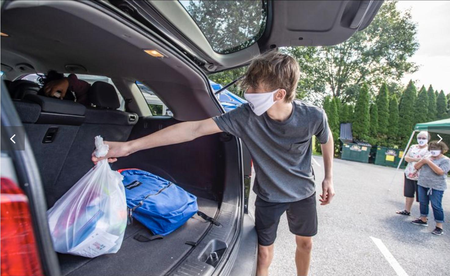 El voluntario Elijah Block, de 13 años, coloca artículos en el vehículo de una familia durante el día de entrega de morrales de la iglesia Wesley Church en Bethlehem, realizado el sábado. Foto de April Gamiz, The Morning Call.