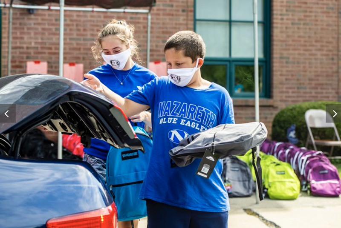 Los/as voluntarios/as Shannon Stivala de 13 años, a la izquierda y Ryan Golinsky, de 11 años cargan morrales de manera segura en el maletero de un automóvil durante el día de entrega de morrales de la iglesia Wesley en Bethlehem, realizado el sábado. Foto de April Gamiz, The Morning Call.