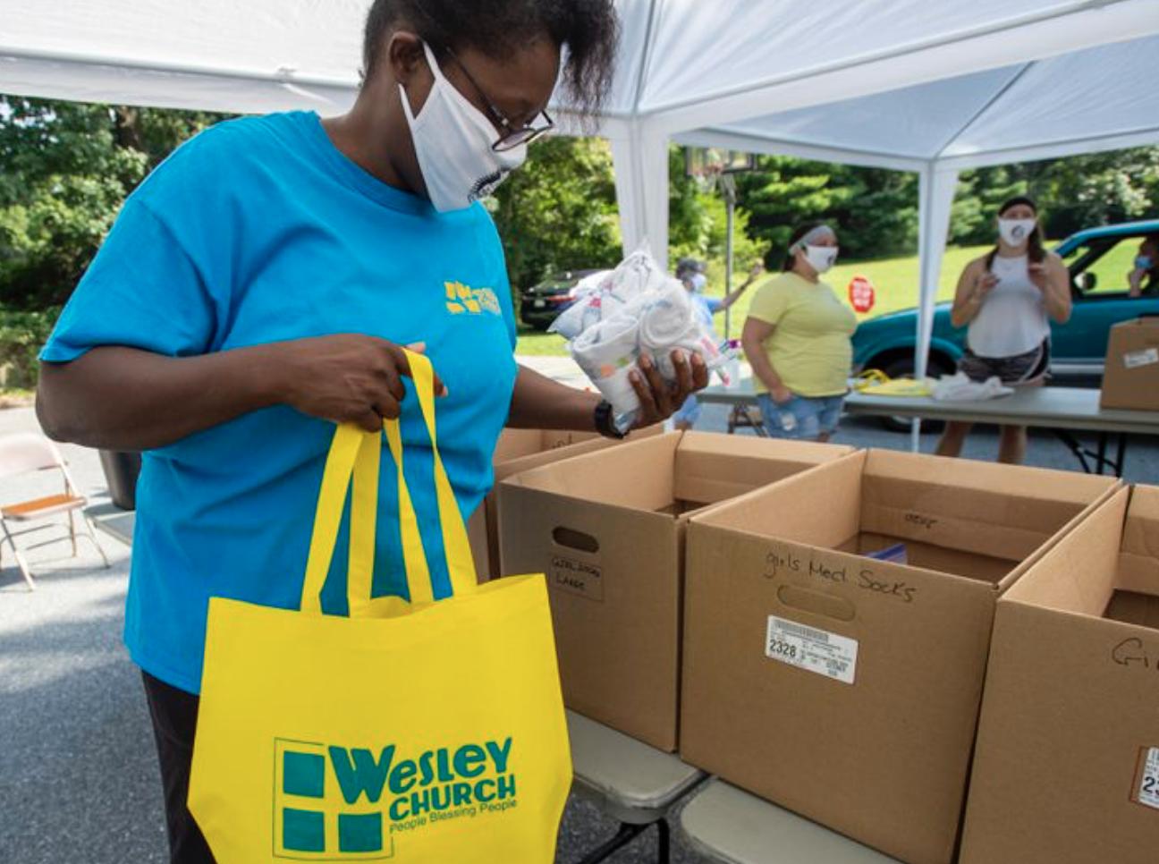 La voluntaria Nicole Lockhart coloca artículos en una bolsa para una familia durante el el día de entrega de morrales de la iglesia Wesley en Bethlehem, realizado el sábado. Foto de April Gamiz, The Morning Call.