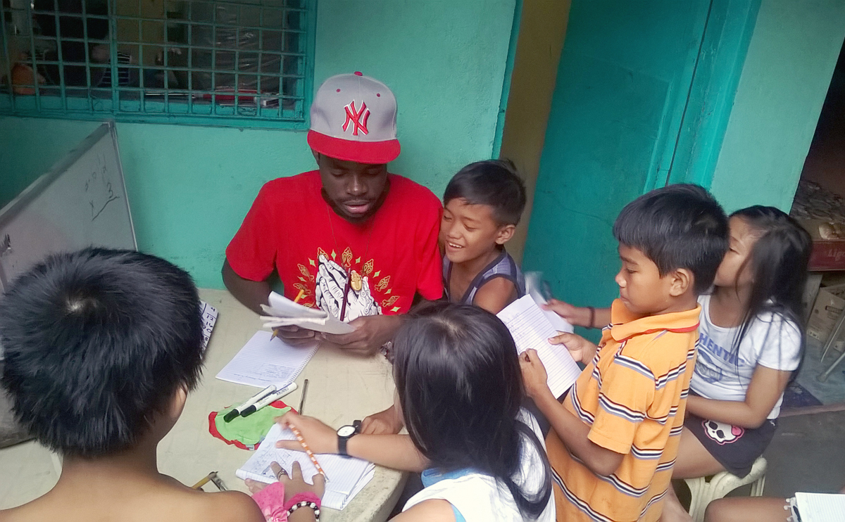 Global Mission Fellow Bellarmee Milosi gives a tutoring session for children in  Tramo, Philippines, as part of the Kapatiran-Kaunlaran Foundation Inc. With the current budget constraints, expansion of this successful young adult ministry is unlikely. 2018 file photo courtesy of Global Ministries.
