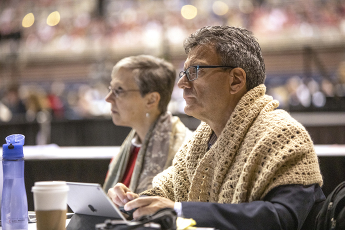Agency top executives Harriet J. Olson with United Methodist Women and Thomas Kemper (wrapped in a prayer shawl) with Global Ministries listen to speakers at the 2019 United Methodist General Conference. Both agencies are coping with decreases in denomination giving  File photo by Kathleen Barry, UM News.