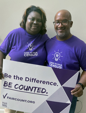 """The Rev. Ralph Thompson (right), senior pastor of Columbia Drive United Methodist Church, and Taressa Thompson, the church's first lady, stand with a Fair Count sign and """"Come To Your Census!"""" T-shirts. The two are working with the nonpartisan nonprofit to make sure people get counted in the census. Photo courtesy of Taressa Thompson."""