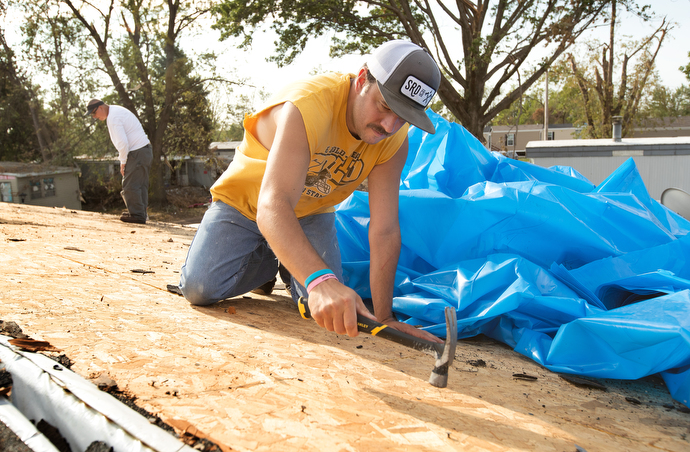 Jesse Parcher flattens roofing nails so they won't tear a plastic tarp while he makes emergency repairs to a storm-damaged home in Marion, Iowa. Parcher was part of a volunteer team working with Marion First United Methodist Church. Photo by Mike DuBose, UM News.