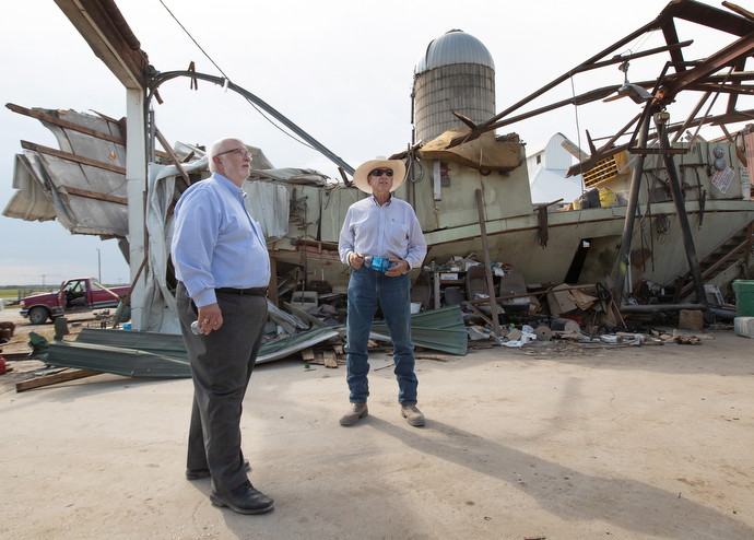 The Rev. Jon Moss (left) visits with Wayne Blackford in what remains of Blackford's farm maintenance shop near Marion, Iowa, following a derecho windstorm Aug. 10. Moss is pastor of Prairie Chapel United Methodist Church in Marion, where Blackford serves as lay leader. Photo by Mike DuBose, UM News.