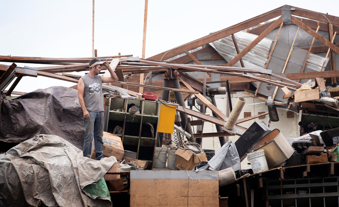 Wyatt Blackford surveys damage caused by a derecho to the maintenance shop at his family's farm near Marion, Iowa. Photo by Mike DuBose, UM News.